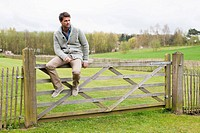 Man sitting on the gate of a cottage