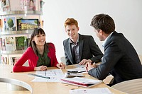 Real estate agent discussing property documents to his clients (thumbnail)