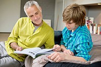 Teenage boy studying with his father at home