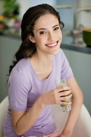 Woman holding a glass of cold soup and smiling (thumbnail)