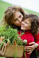 Boy holding a crate of vegetables with his mother kissing him