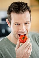 Man eating a tomato