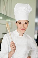 Happy female chef holding a wooden spoon (thumbnail)