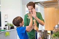 Man and son giving high five to each other in the kitchen