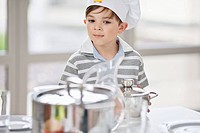 Boy placing pans on a dining table