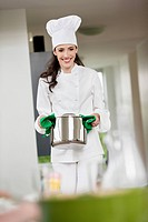 Female chef carrying a saucepan
