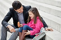 Man sitting with his daughter eating pain au chocolat