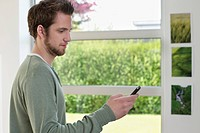 Man standing near a window using a mobile phone