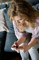 Woman text messaging on a mobile phone at home