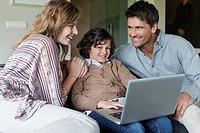 Boy using a laptop with his parents at home