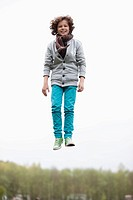Portrait of a boy jumping in a field (thumbnail)