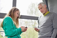 Man and daughter using their mobile phones