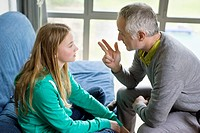 Man discussing with his daughter at home