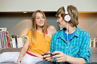 Teenage boy listening to music on iPod with his sister at home (thumbnail)