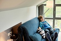 Teenage boy sleeping on a couch at home