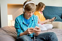 Teenage boy listening to music on iPod with his sister using digital tablet