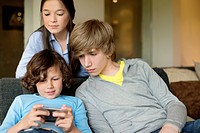 Boy using a cellphone with his brother and sister at home