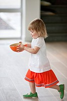 Girl carrying a bowl of food