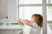 Cute little girl picking up toy tea set from a dining table