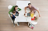 High angle view of couple with their children at study table