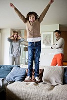 Naughty boy jumping on couch with his parents in the background