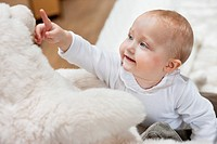 Close_up of a baby girl playing with a teddy bear