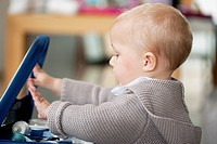 Close-up of a baby girl playing (thumbnail)