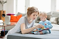 Woman showing a picture book to her daughter