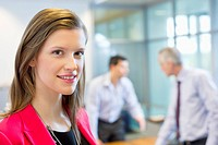 Portrait of a businesswoman smiling in an office with her colleagues discussing in the background