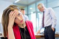 Female executive looking sad in an office with her colleagues discussing in the background (thumbnail)