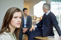 Female executive thinking in an office with her colleagues discussing in the background