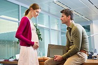 Pregnant woman with her colleague in the office