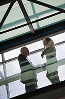 Low angle view of two business executives talking (thumbnail)