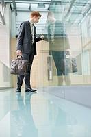 Businessman peeking through glass in a corridor