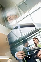 Reflection of business executives on window glass