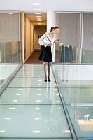 Businesswoman peeking through glass in a corridor