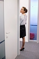 Businesswoman peeking through a door in a corridor (thumbnail)