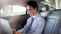 Businessman using laptop in back seat of car