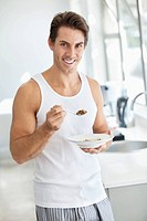 Portrait of smiling man eating cereal in kitchen
