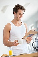 Smiling man drinking coffee and reading newspaper in kitchen