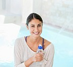 Portrait of smiling woman with water bottle at poolside