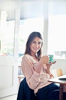 Portrait of smiling businesswoman drinking coffee