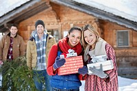 Portrait of smiling friends holding Christmas gifts in front of cabin (thumbnail)