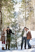 Portrait of smiling couples with fresh cut Christmas tree in woods (thumbnail)