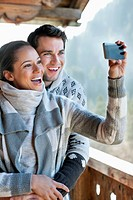Smiling couple taking self_portrait with camera phone on cabin porch