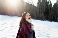Portrait of smiling woman walking in snowy field