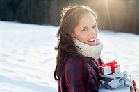 Portrait of smiling woman holding Christmas gifts in snow (thumbnail)