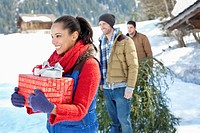 Smiling friends with fresh cut Christmas tree and gifts in snow (thumbnail)
