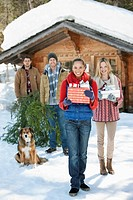 Portrait of smiling couples and dog with fresh cut Christmas tree and gifts in front of cabin