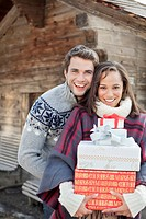 Portrait of smiling couple holding Christmas gifts in front of cabin